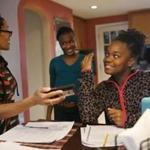Danita Brewster laughed as she pulls out a video of a choreographed routine her adopted daughters Ty-Janee, 12, and Que-Mya, 11, have to learn as her biological son, Arthur James Brewster III, made brownies in the kitchen at their home in Boston.